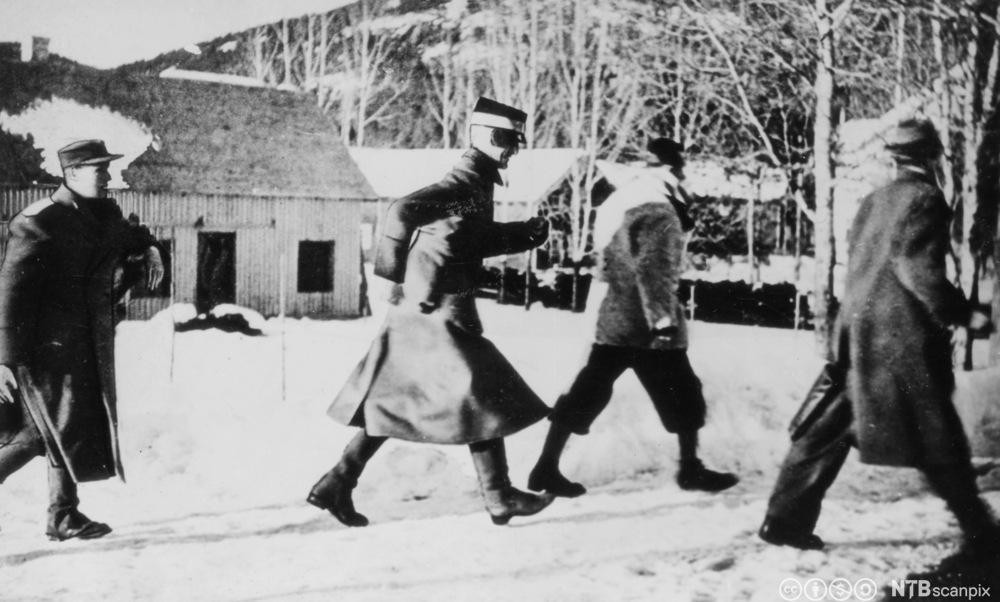 Kong Haakon VII og kronprins Olav (t.v.) under flukten nordover. Kongen og kronprinsen med følge løper her mot skogen for å søke dekning for det tyske flyangrepet på Nybergsund 11. april 1940.