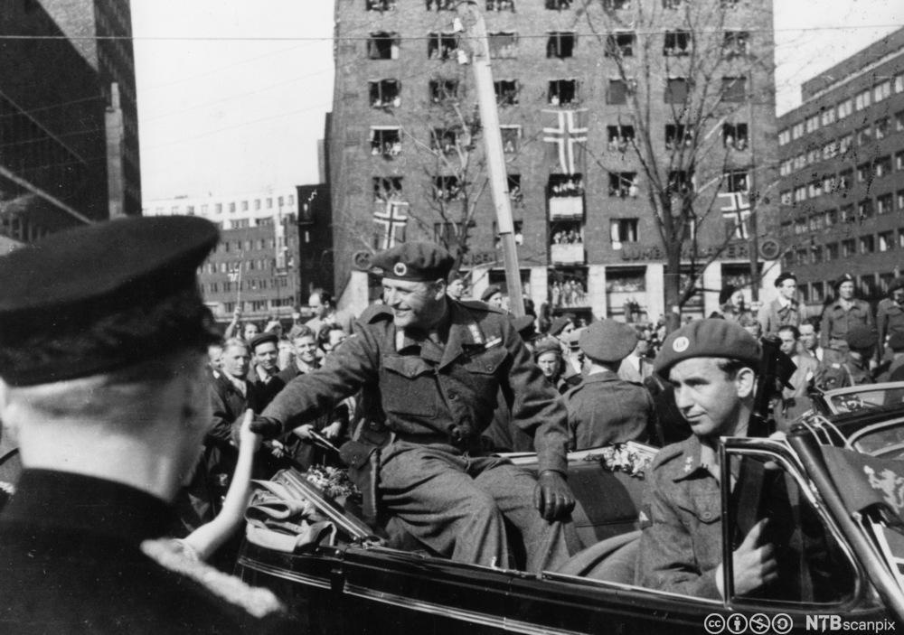 Kronprinsen i åpen bil etter frigjøringen av norge. Max Manus i forsetet er bevæpnet livvakt