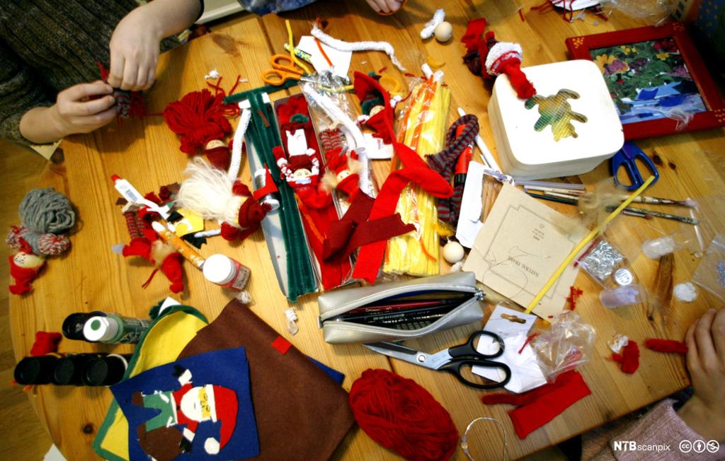 bord der det jobbes med å lage julepynt. Foto.