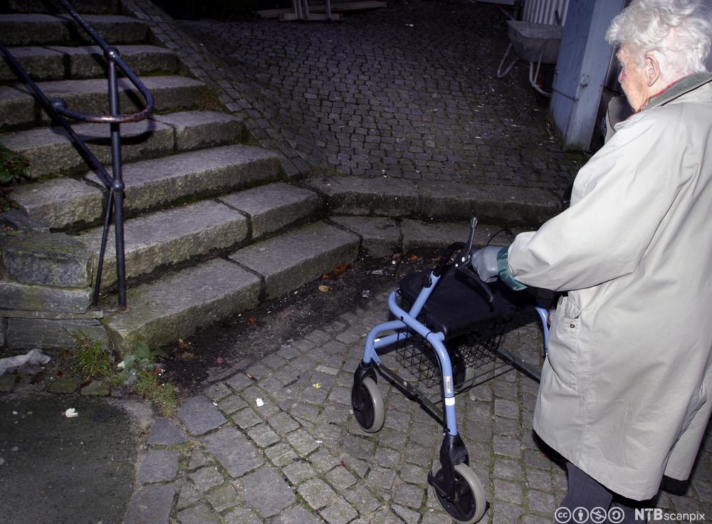 Eldre kvinne stopper ved en en trapp