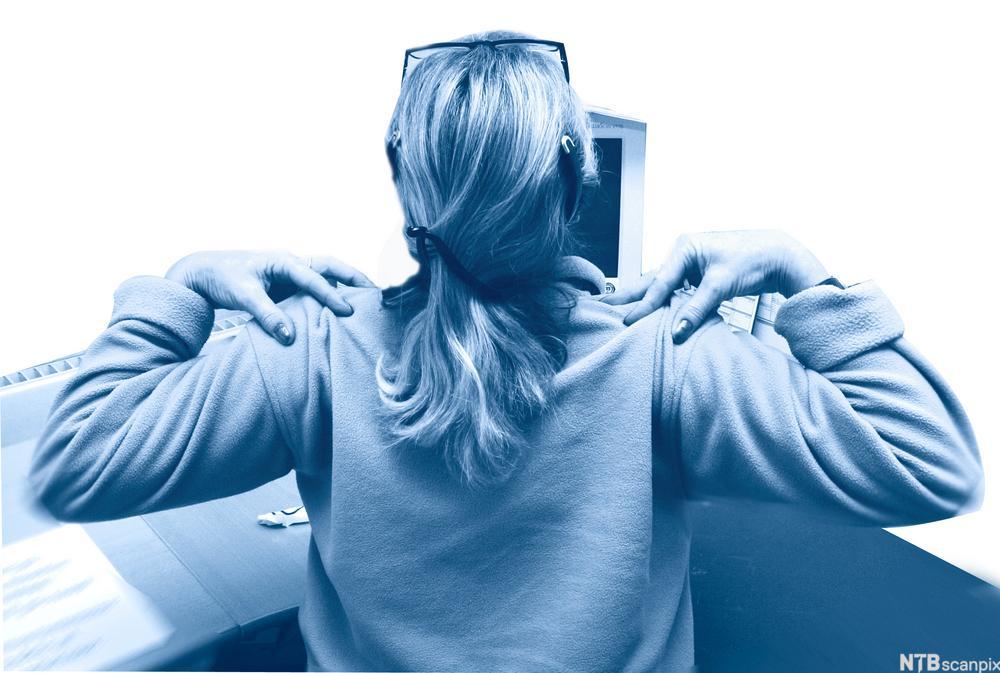 Kvinne som gjør en armøvelse ved arbeidsplassen sin. Foto