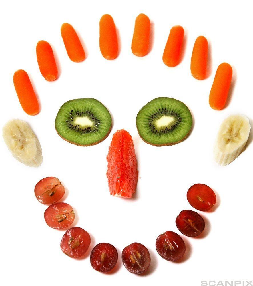 Oppkutta frukt lagt i eit mønster som illustrerer eit ansikt. Foto.