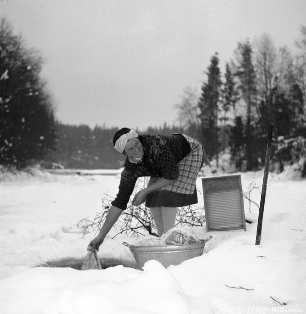 Kvinne vasker klær i en bekk. Foto.
