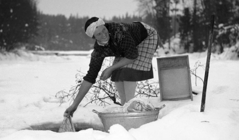 Kvinne vasker klær i et hull i isen i en bekk. Foto.