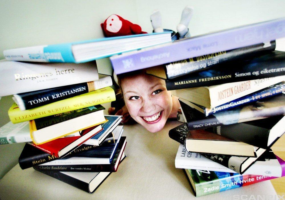 Kvinne omgitt av gratisbøker fra bokklubber. Foto.