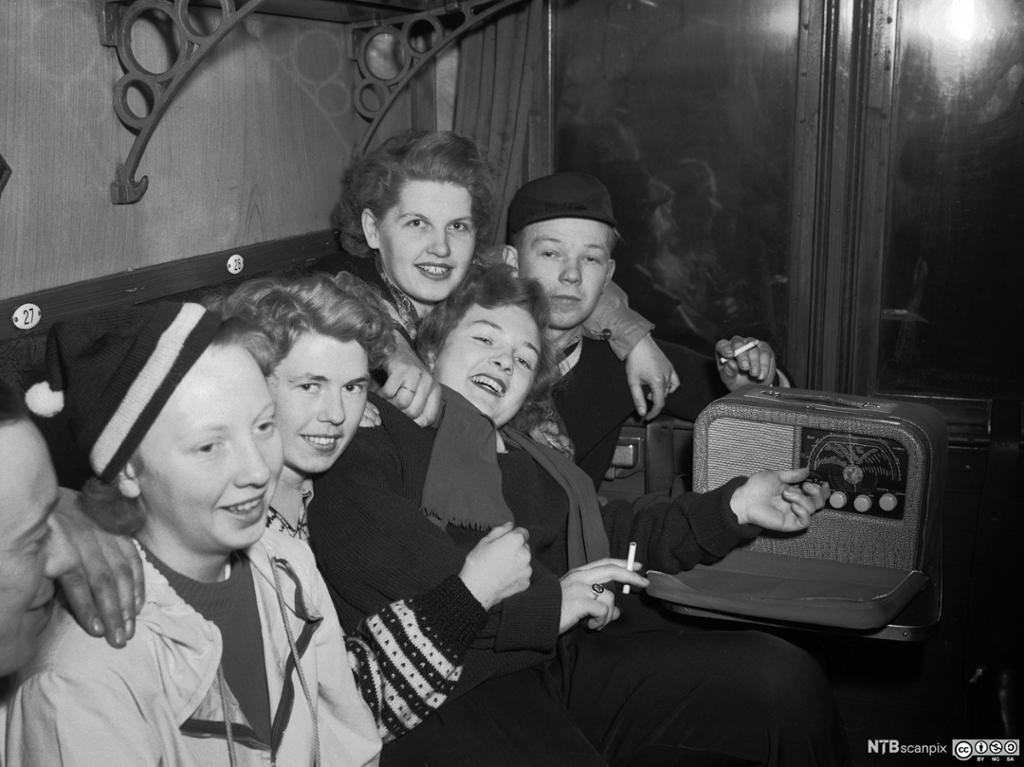 En gjeng ungdommer som sitter på toget og lytter til en Kurer reiseradio. Bilde.