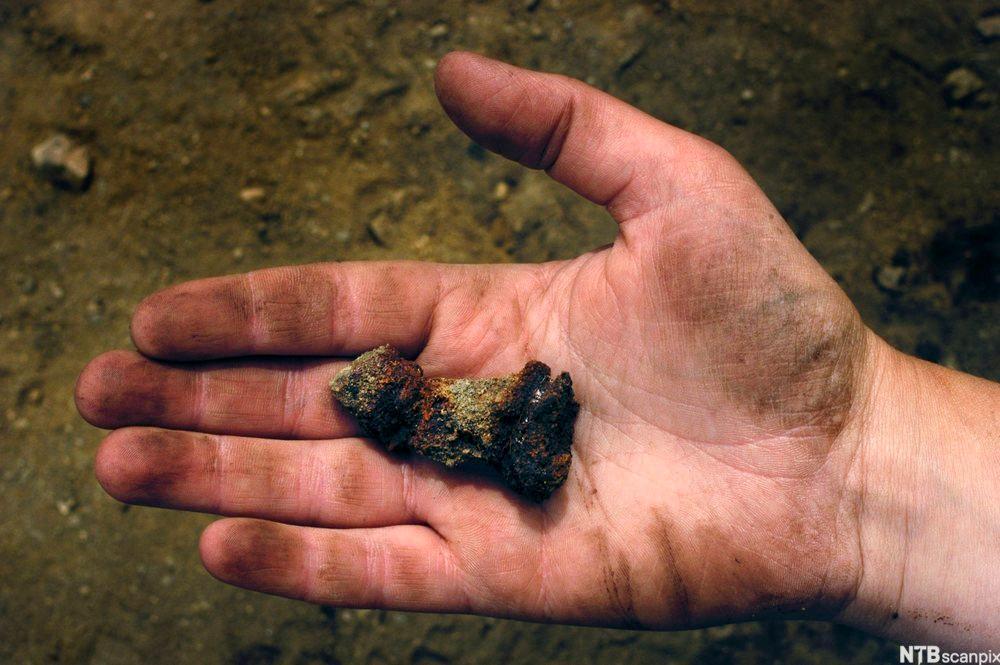 En hånd med ubestemmelige klumper. Foto.