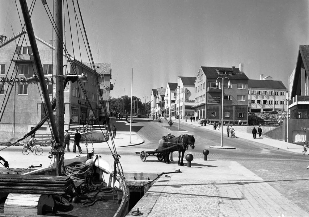 Historisk bilde fra bymiljø med seilbåt ved brygge og hest med kjerre i gaten.foto.