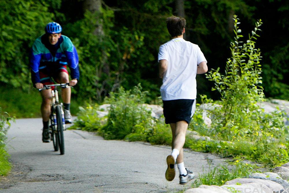 En syklende og en joggende langs landevei. Foto.