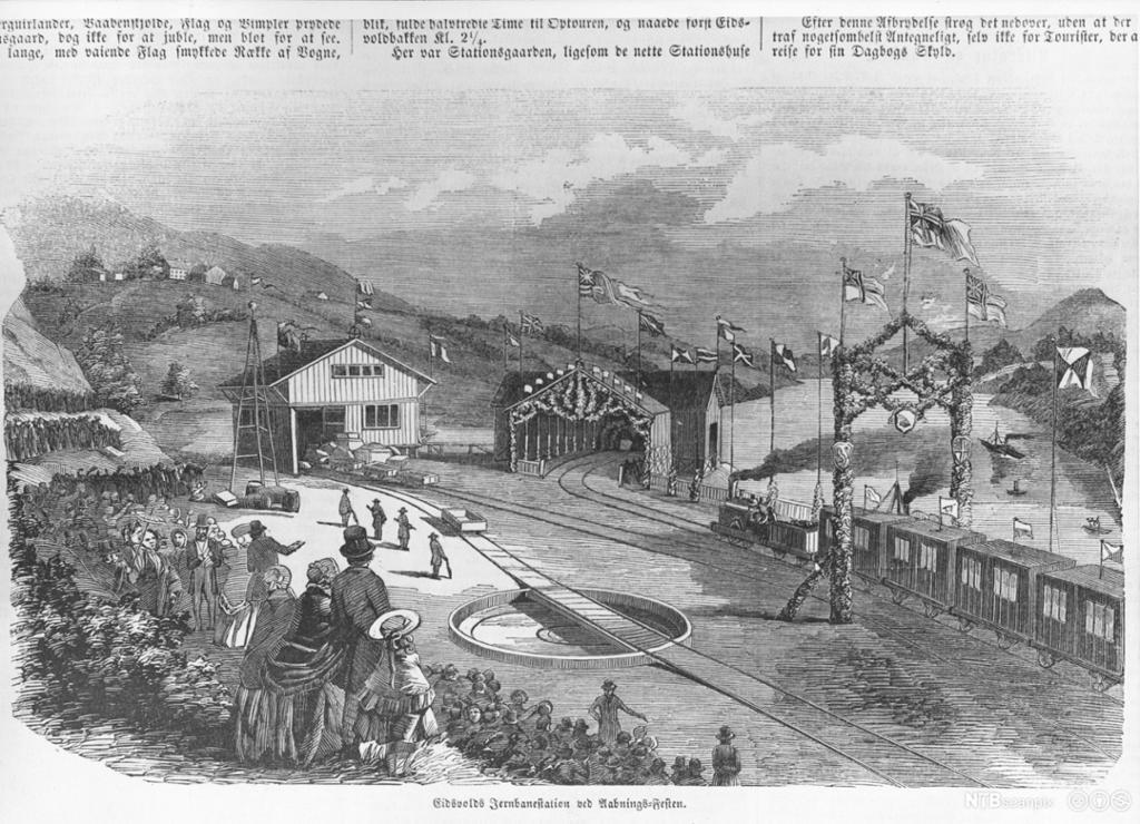 Festpyntet folkemengde, portal med vaiende flagg over togskinner, stasjonsbygninger og tog.  Avistegning.