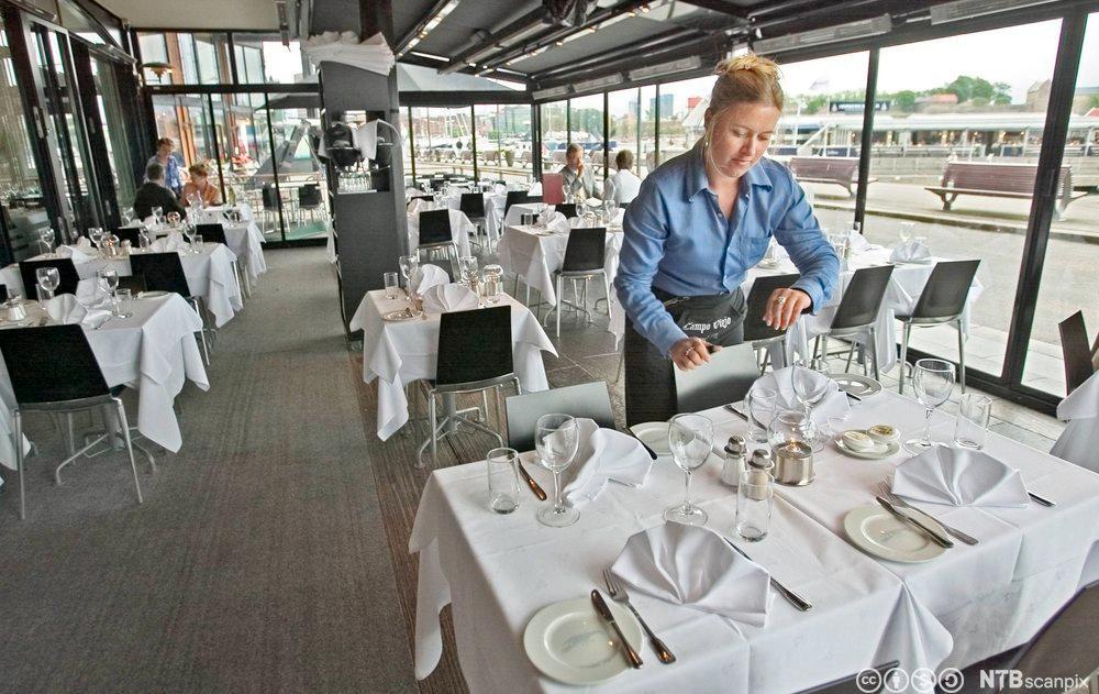 Servitør dekker bord. Foto