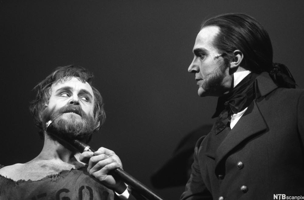 Helten i musikalen Les Miserables, Jean Valjean, og hans hovedmotstander, politimester Javert. Javert  presser skaftet av sabelen sin mot Jean Valjeans hals og truer ham. Foto.
