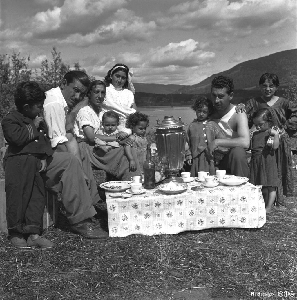 Fra den såkalte sigøynerleiren, romleir, på Vingnes i Lillehammer i 1955. Familie spiser i det fri. Foto.