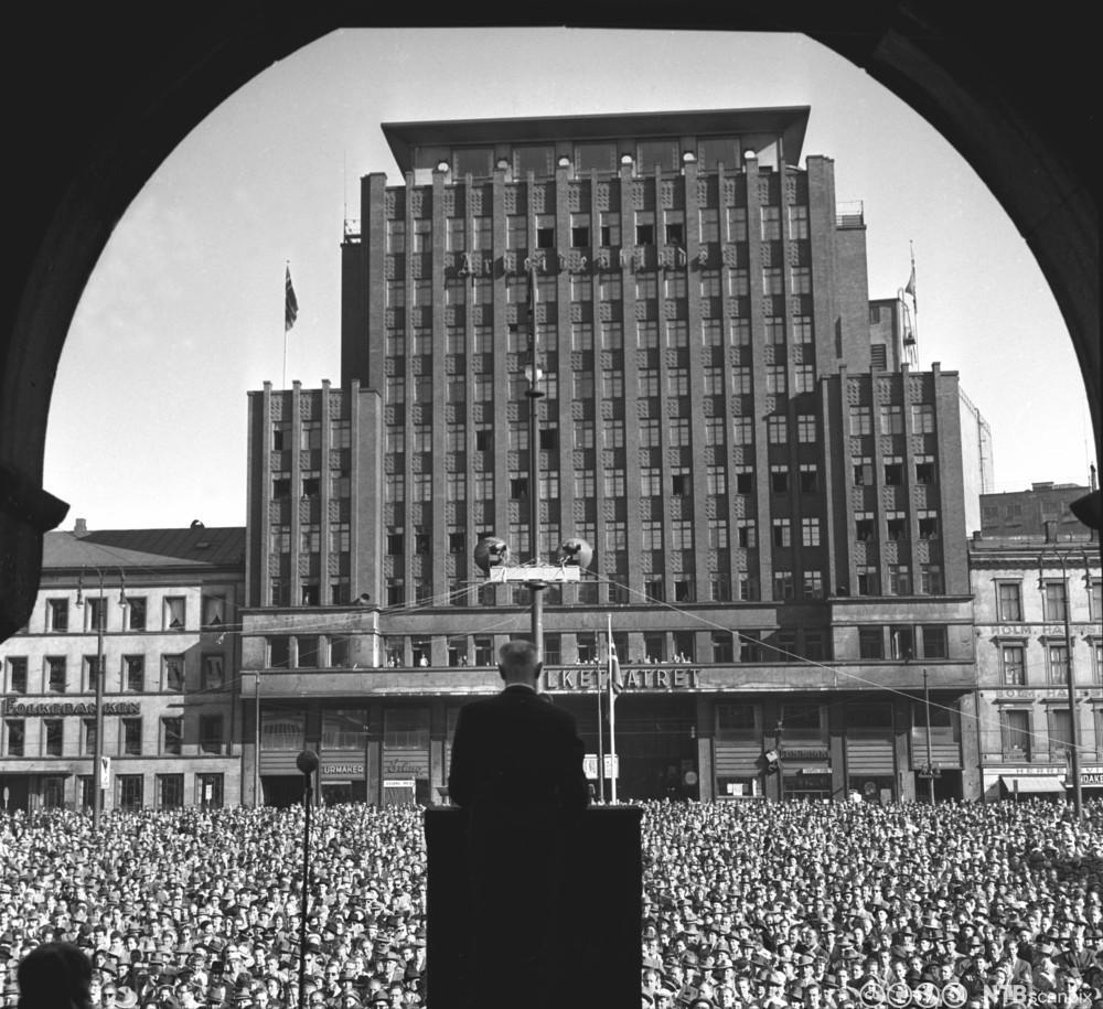 Einar Gerhardsen taler på Youngstorget 1. mai 1957. Vi ser Gerhardsen med ryggen til foran en stor folkemengde. Foto.