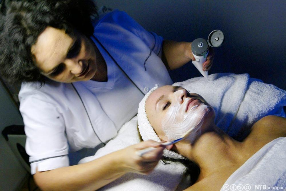 En hudpleier som legger en maske. Foto.