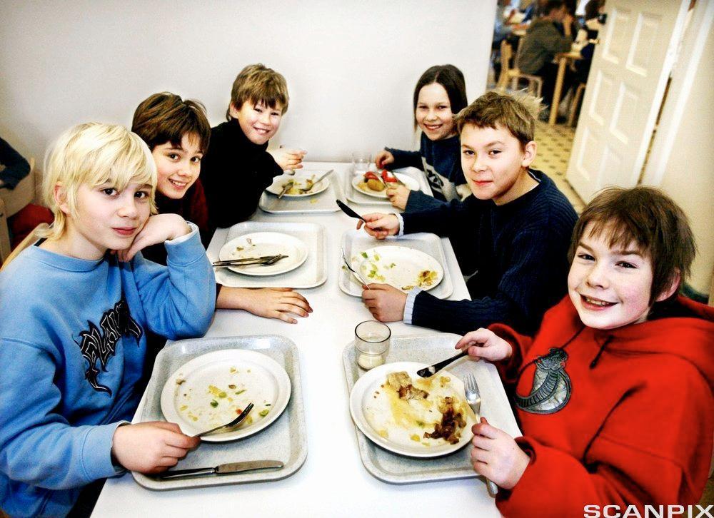 Barn som sitter ved bordet og spiser. Foto.