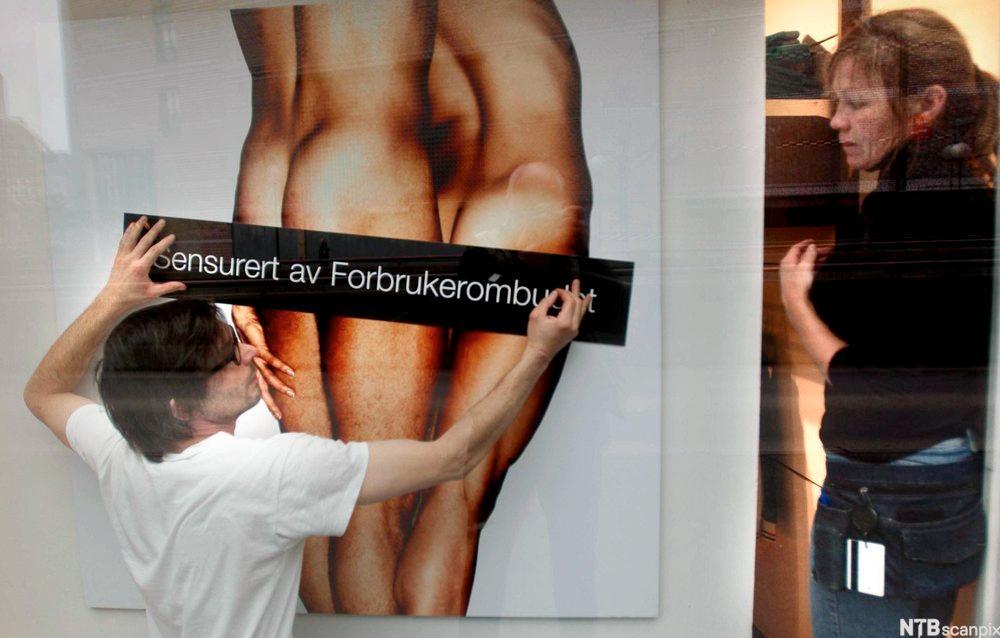 """To kunstnere som sensurerer en reklameplakat med bilde av to nakne mennesker ved å feste et stort, svart klistremerke med påskriften """"Sensurert av Forbrukerombudet"""" tvers over plakaten. Foto."""