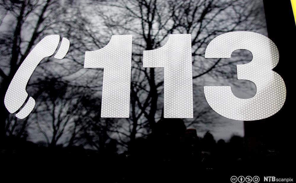 Nummer 113 og illustrasjon av telefon på bilrute. foto.