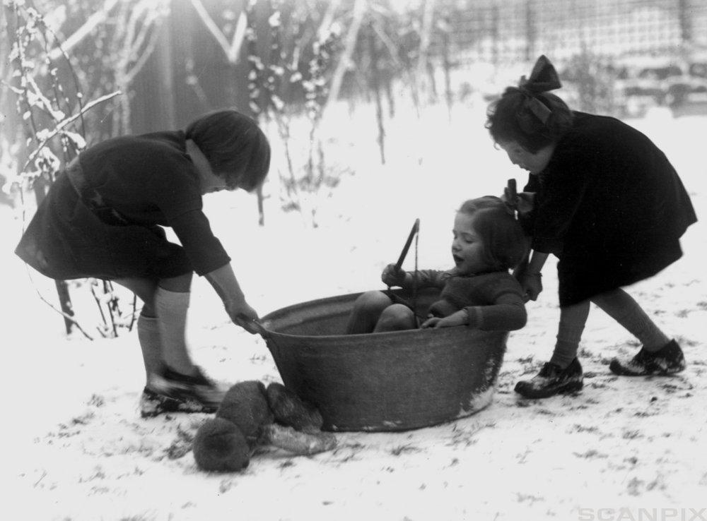 Barn i 1920 som leker i en vaskebalje. Foto.