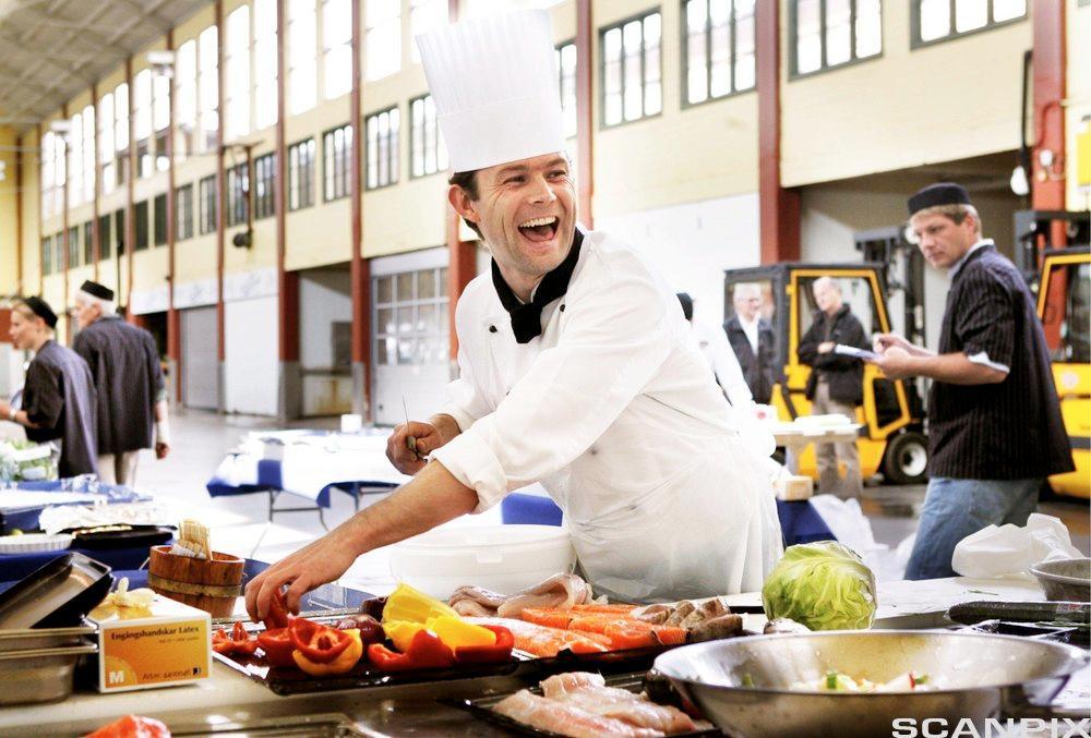 Kokk står ute i en hall og lager mat med fisk og grønnsaker. Foto.