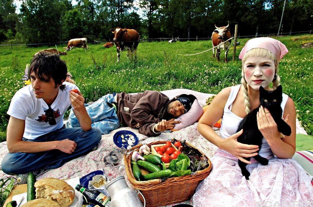 Artistar får servert økologisk mat på Ramme gard. To ungdommar er ute på piknik, og vi kan sjå nokon kyr som et gras bak dei. Foto
