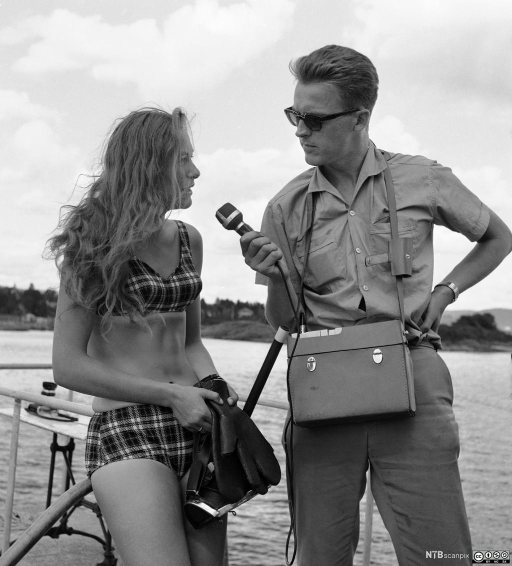 Radioreporter intervjuer ung kvinne i bikini. Foto.