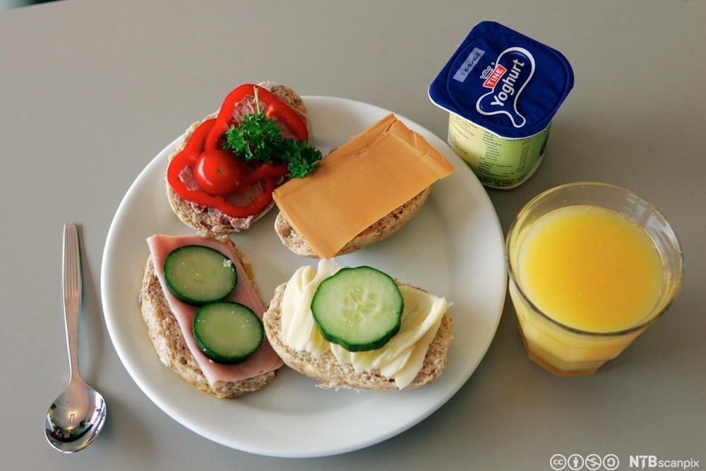 Mat på et fat med et glas juice og en yougurt ved siden av. Foto.