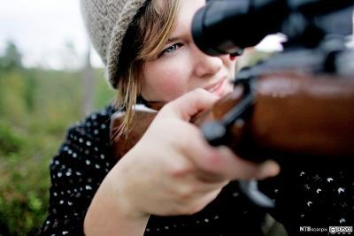 Ung kvinne ser i geværsikte. Foto.