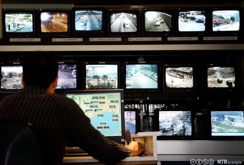 Mann som følger med på mange videoskjermer. Fotografi.