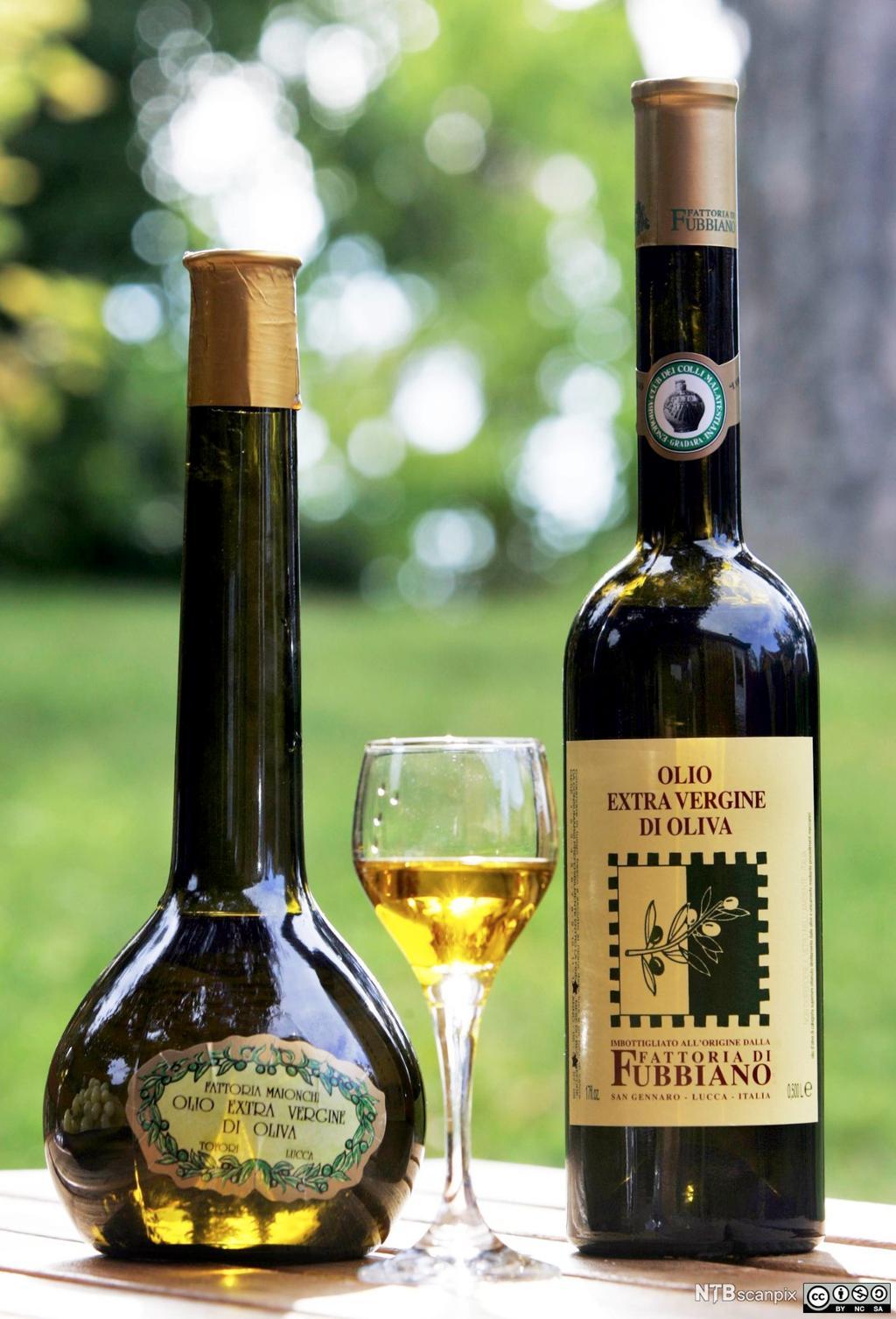 To flasker eksklusiv olivenolje og et stettglass med litt olivenolje i. Foto