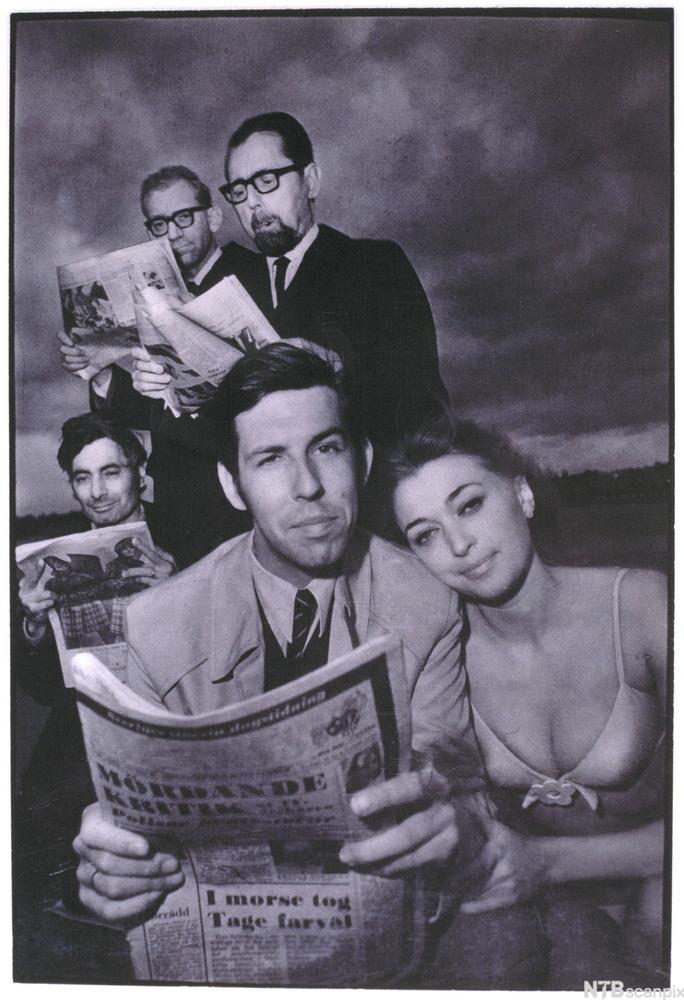 Dresskledde menn og lettkledd kvinner med avis. Foto