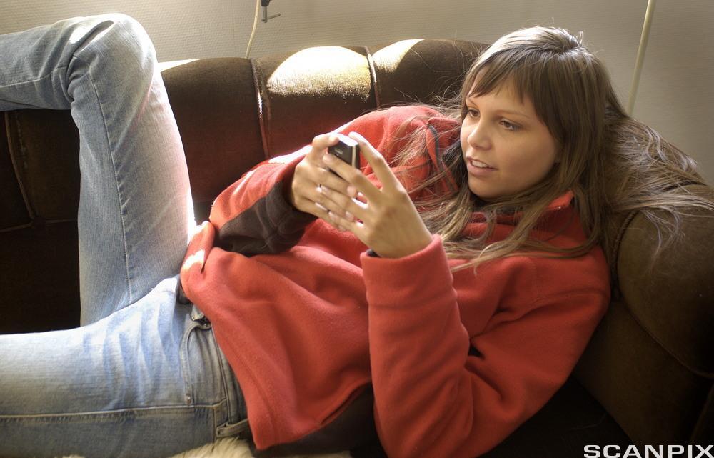 Ung jente med mobiltelefon sender SMS. Foto.