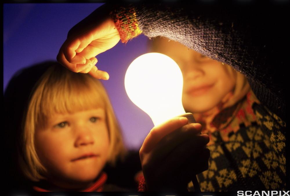 Barn med lyspære. Foto.