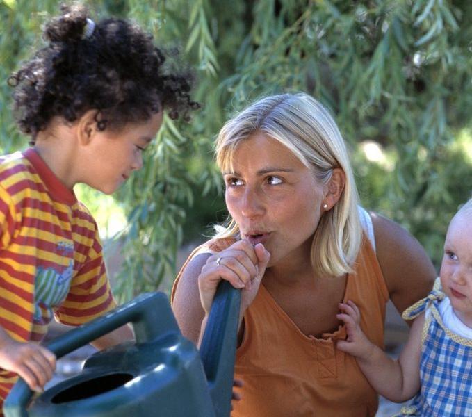 Kvinne leker med to små barn. Foto.