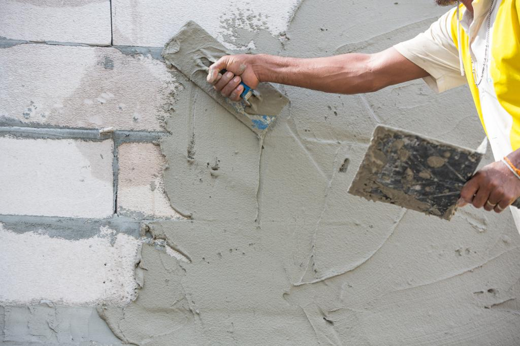 Murer legger mørtel på en murvegg. Foto.