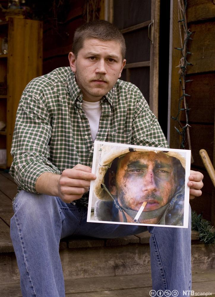 Den tidligere soldaten Blake Miller med et fotografi av seg selv fra dokumentaren The Marlboro Marine. Fotografi.