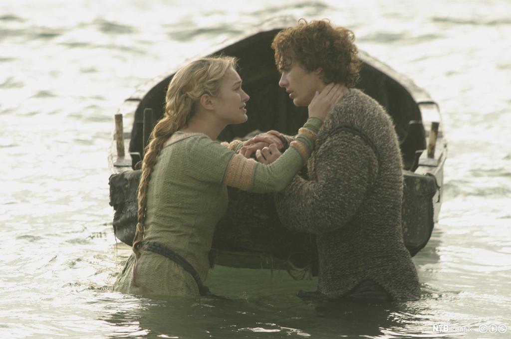 Tristan og Isolde står ved en pram, noen meter uti vannet, og holder hverandres hender. Stillbilde fra film..