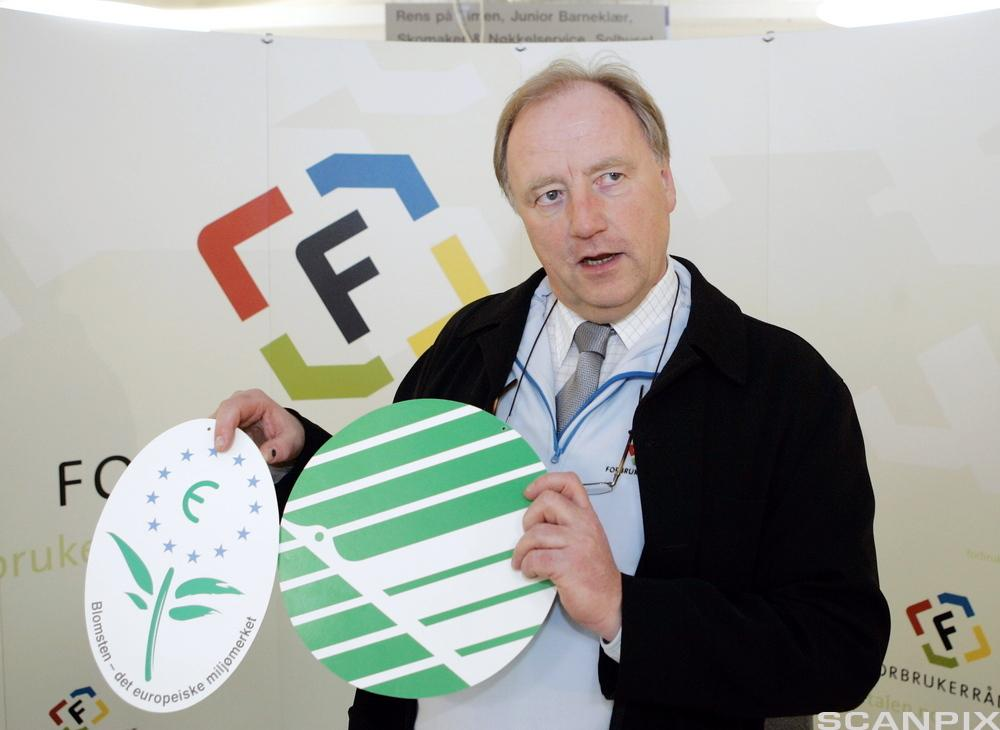 Mann holder opp to sirkelformede papplater med logoene for det europeiske miljømerket EU-blomsten og det nordiske Svanemerket. Foto.