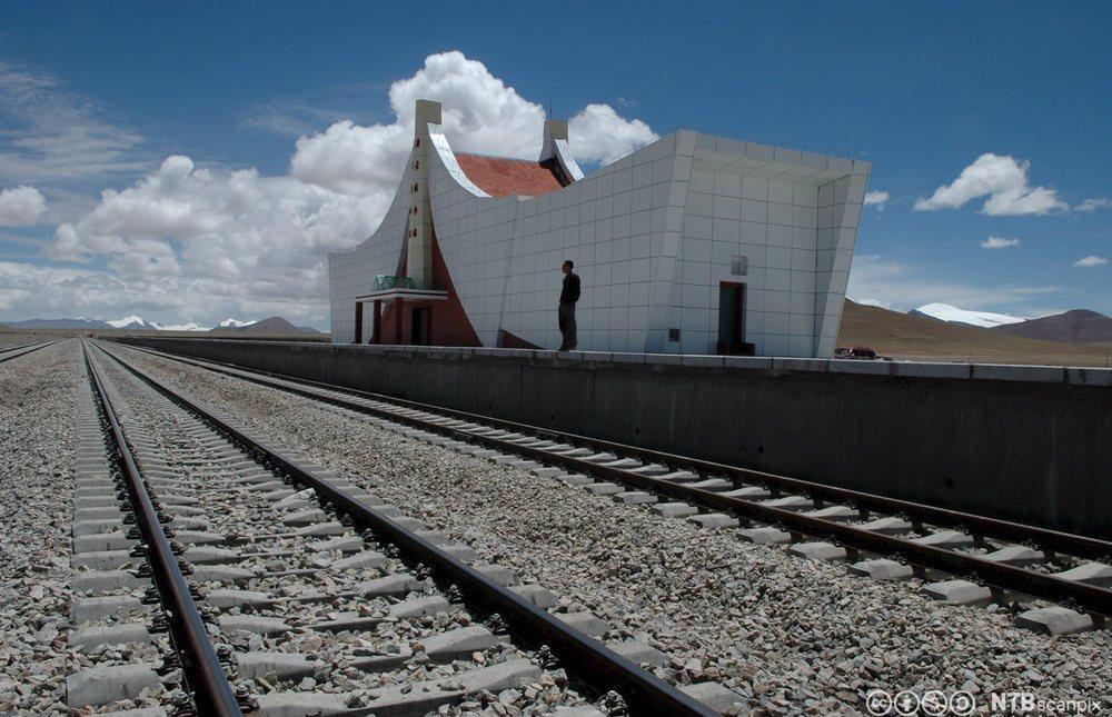 Hvit bygning med togskinner foran. Foto.