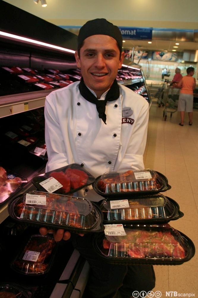 En ferskvaresjef holder en rekke emballerte kjøttprodukter i hendene sine. Foto.