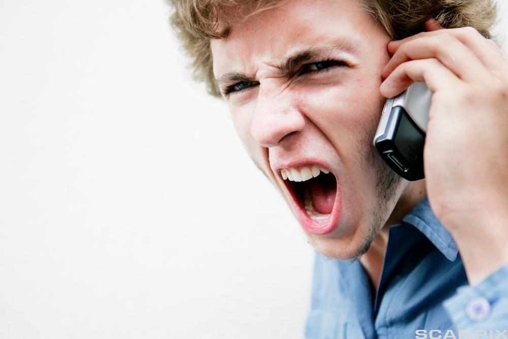 Bilde av en sint mann på telefon.