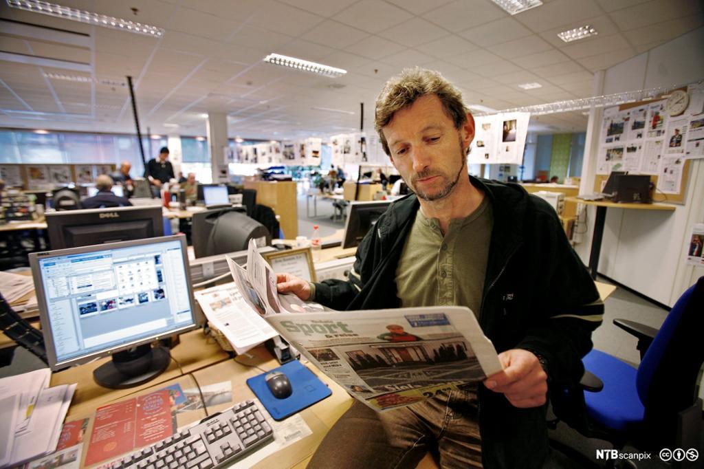 Mann leser avis i redaksjonslokale. Fotografi.