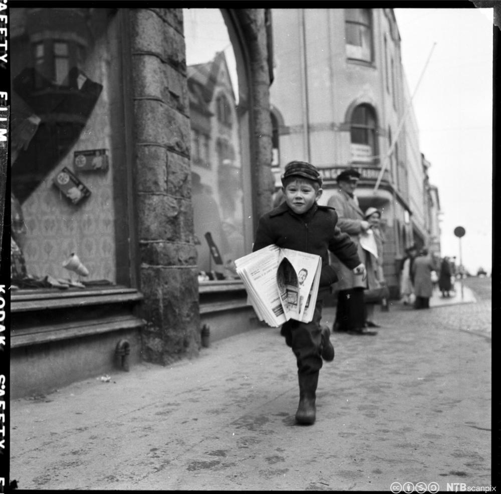 En gutt løper i gata og selger aviser. Foto.