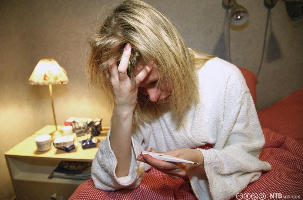 Kvinne sitter i senga og ser på et termometer. Foto.