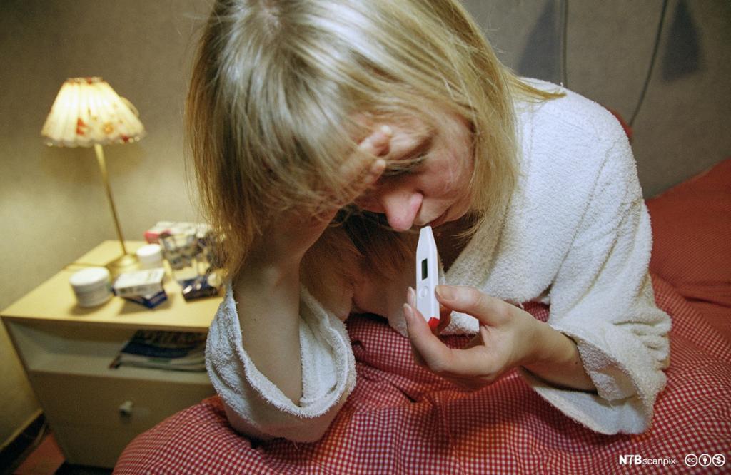 Syk dame måler feberen. Foto.
