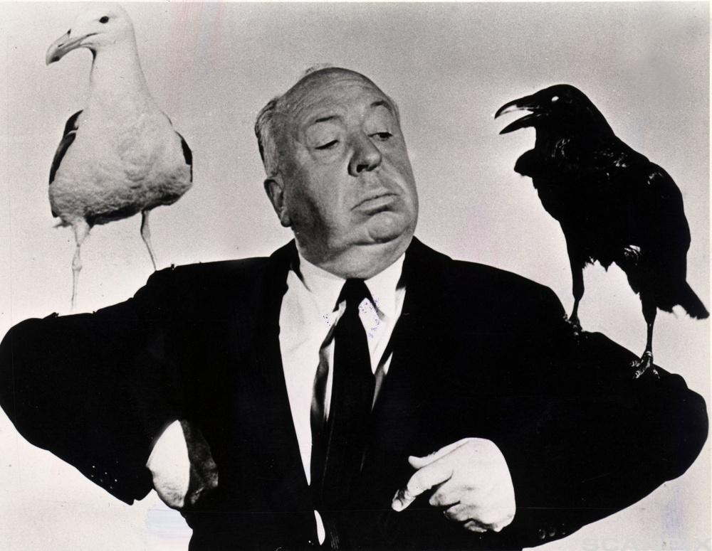 Alfred Hitchcock med en hvit måke og en svart ravn på skudleren. Foto.