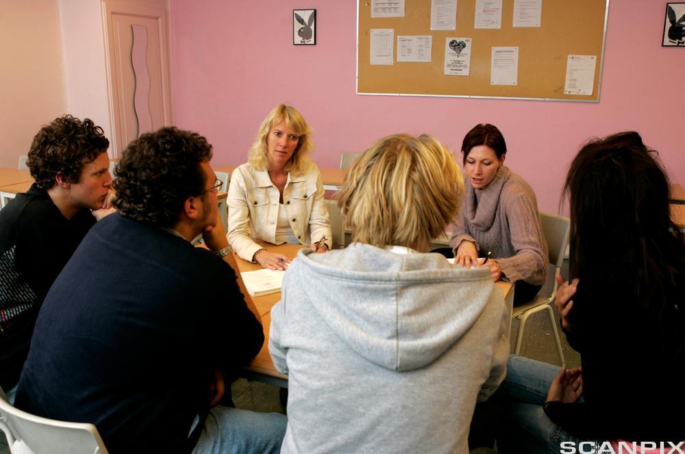 Gruppe mennesker rundt et bord. Foto.