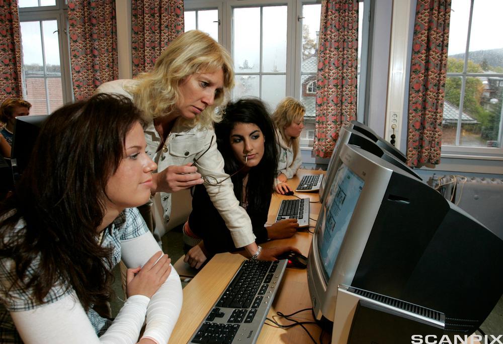 Lærer veileder elever foran dataskjerm i klasserom. foto.