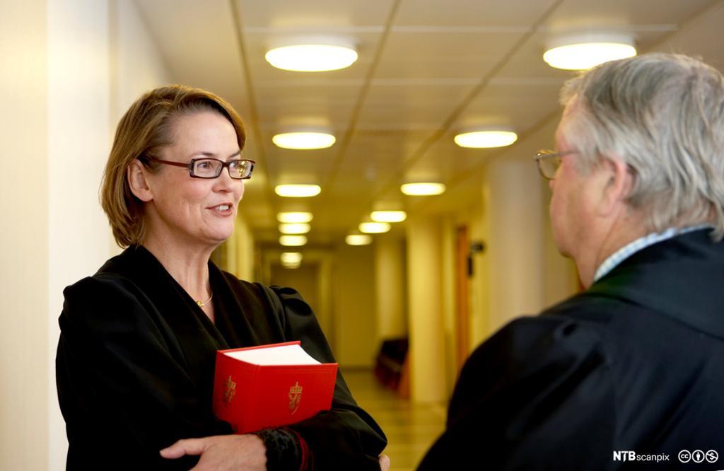 Jurist med Norges lover i hendene. Foto.