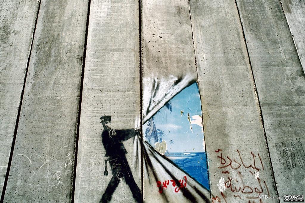 En politimann som åpner opp utsikten bak en vegg. Grafitti.
